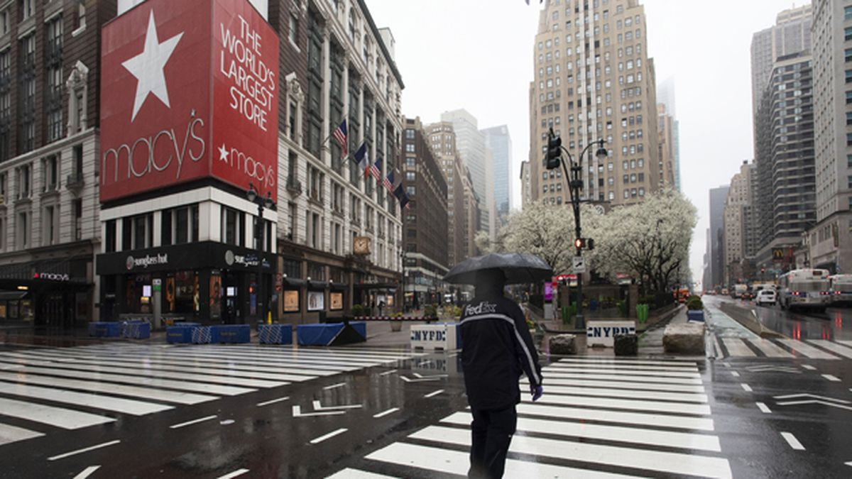 A man crosses the street in front of Macy's, Monday, March 23, 2020 in New York. Macy's stores nationwide are closed due to the coronavirus. (AP Photo/Mark Lennihan)