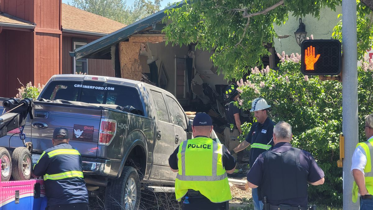 Crews remove a truck that crashed into a home