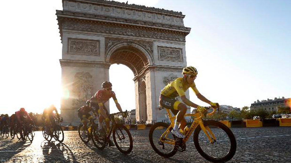Colombia's Egan Bernal wearing the overall leader's yellow jersey, center, rides past the Arc...