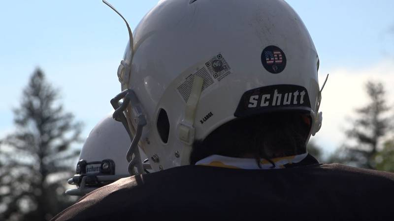 A Centennial Junior High football player stands with his helmet adorned with a sticker to honor...