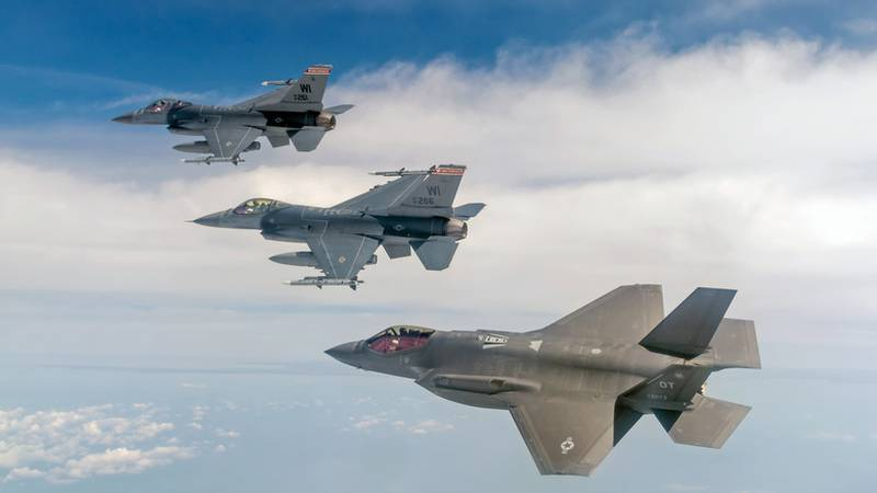 F-16 Fighting Falcons from Madison, Wis. fly alongside an F-35 Lightning II. The Department of...