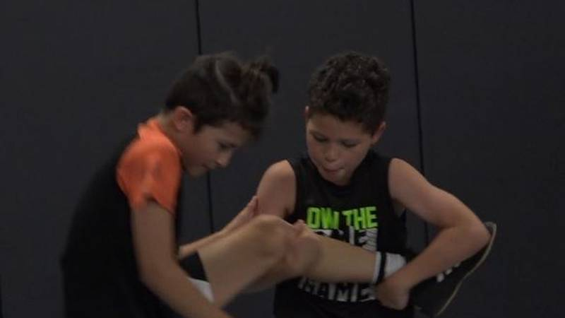 Two young wrestlers practice moves taught to them during the Windy City Wrestling Club summer...