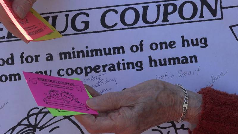 Selma Schneider shows Wyoming News Now the Free Hug Coupons she gives community members