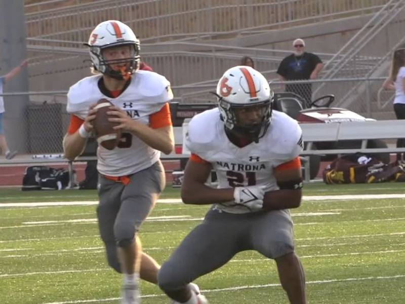 Natrona County Quarterback Tyler Hill drops back to pass after faking a handoff to Running Back...