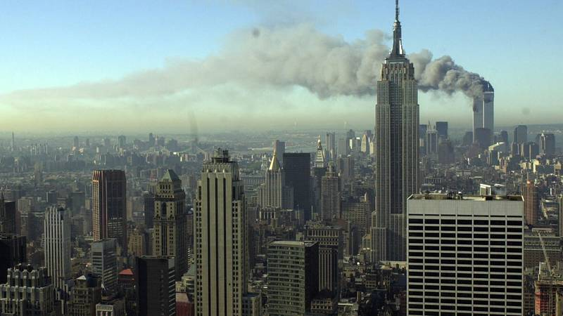 Smoke billows across the New York City skyline after two hijacked planes crashed into the twin...