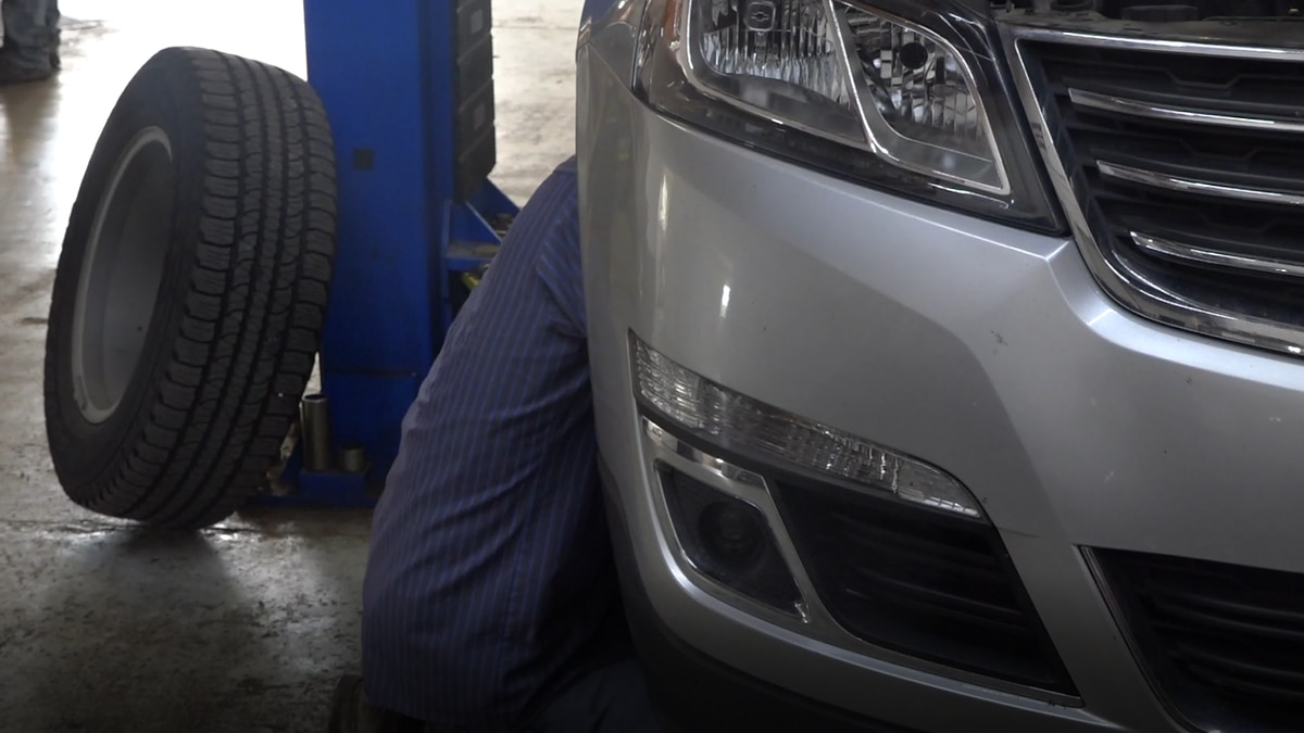 A mechanic at Chuck's auto repair helps fix a car