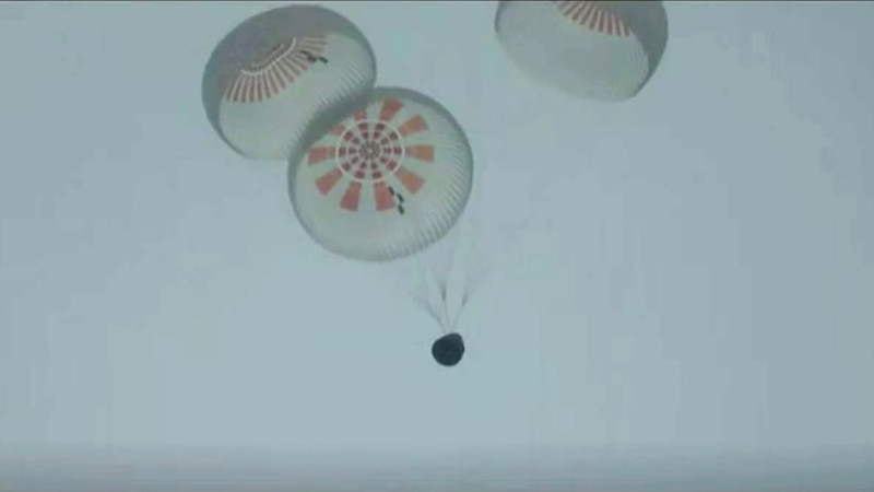 In this image taken from SpaceX video a SpaceX capsule carrying four people parachutes into the...