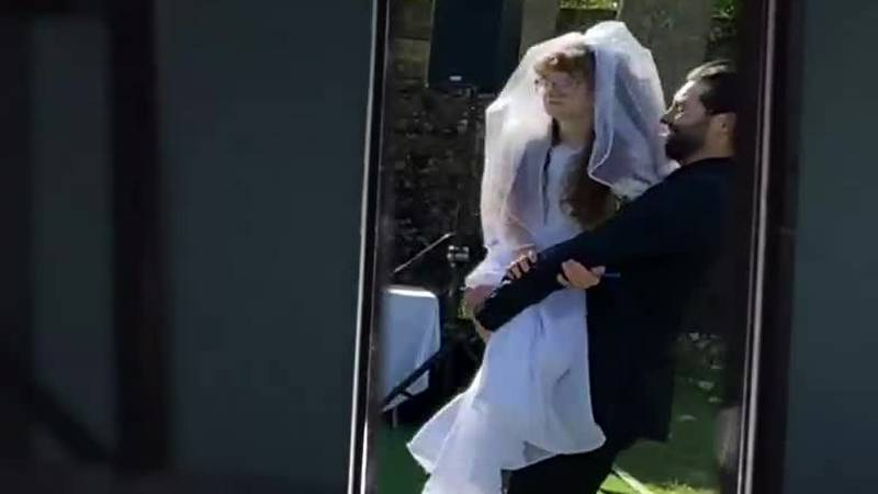 A wedding video showing the groom walking down the aisle holding his sister-in-law is going...