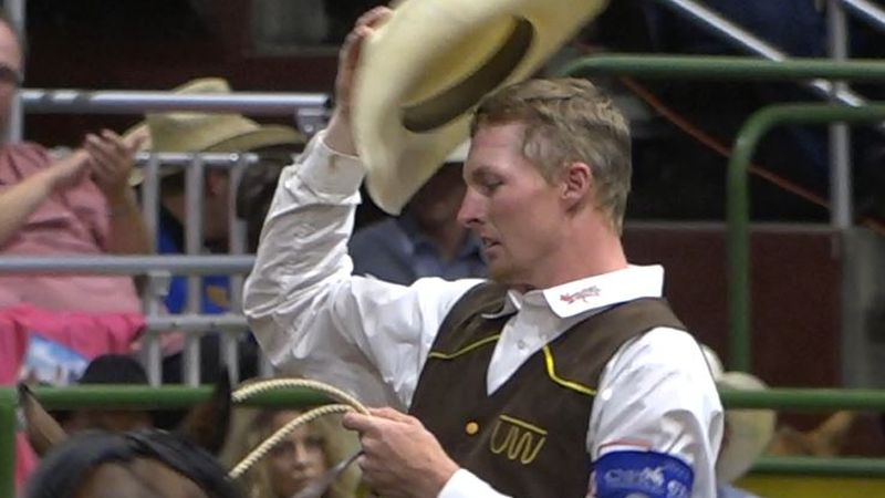 University of Wyoming Cowboy Seth Peterson tips his hat to the crowd after tying down his calf...