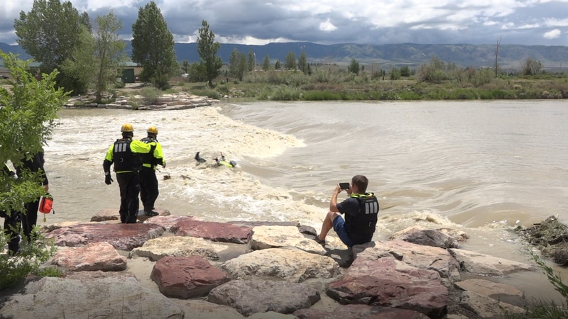 Firefighters throw out a rope to practice saving people in fast moving water
