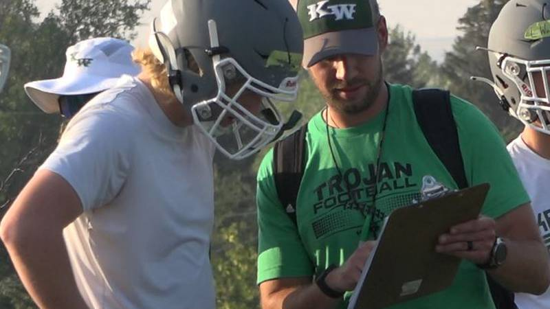 Kelly Walsh Head Football Coach Aaron Makelky walks through something with one of his linemen...