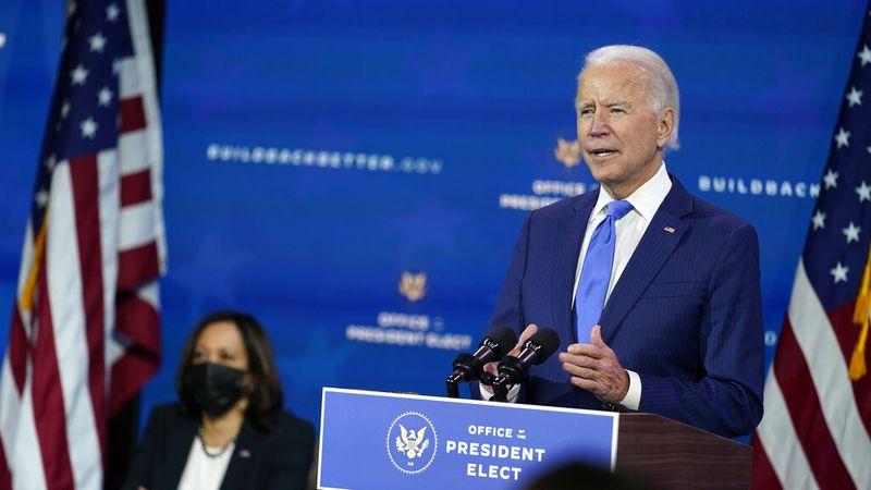 President-elect Joe Biden speaks as Vice President-elect Kamala Harris listens at left, during...
