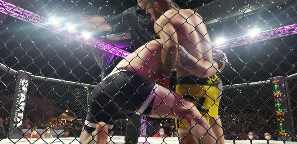 Colorado Fighters jock for position near the cage
