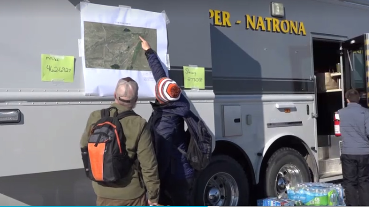 Volunteers check a map before they go out and search for Joey Peterson