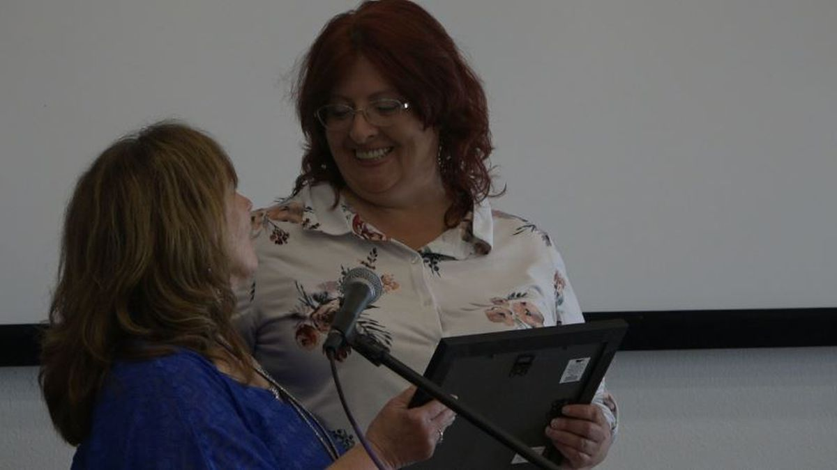 Heather Johnson (R) gets a certificate for graduating phase II of the WRM recovery program