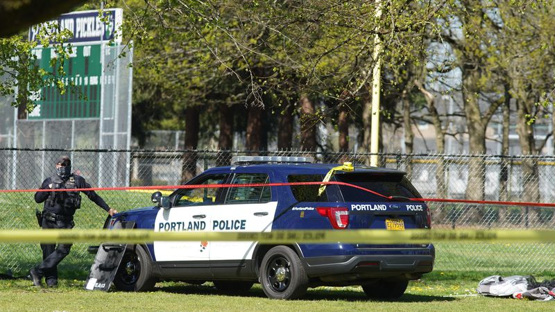 A Portland Police officer stand by following a police involved shooting of a man at Lents Park,...