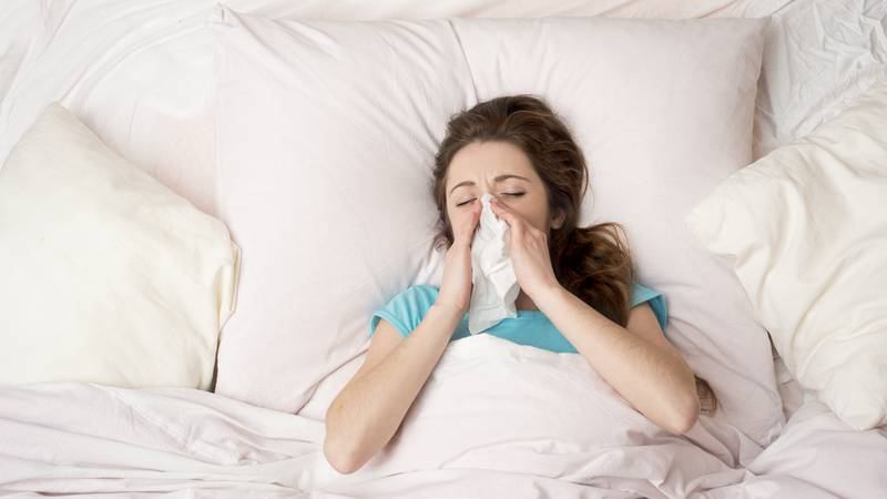 Sick woman lying in bed with high fever. She is blowing nose.